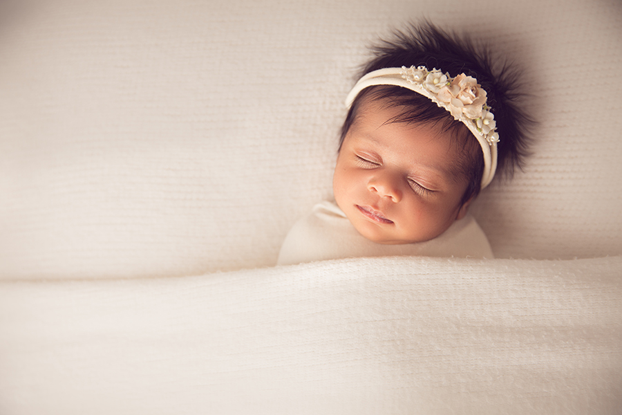 Newborn photography of baby wrapped and tucked under a white blanket wearing a white headband